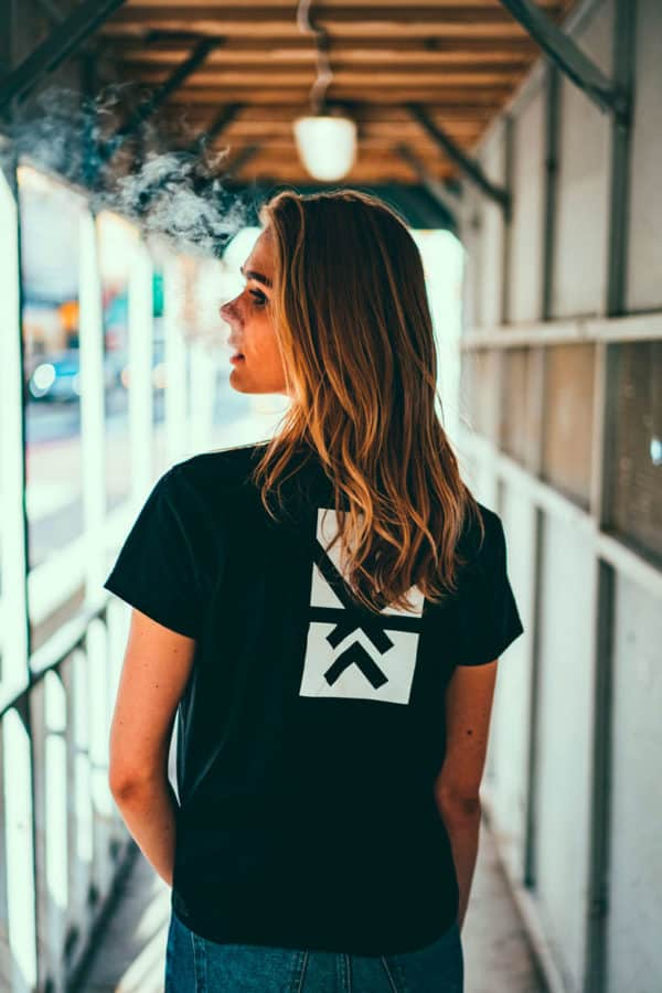 a girl with yellow hair, showing her back, wearing a black t-shirt, with Project Cannabis logo on the t-shirt