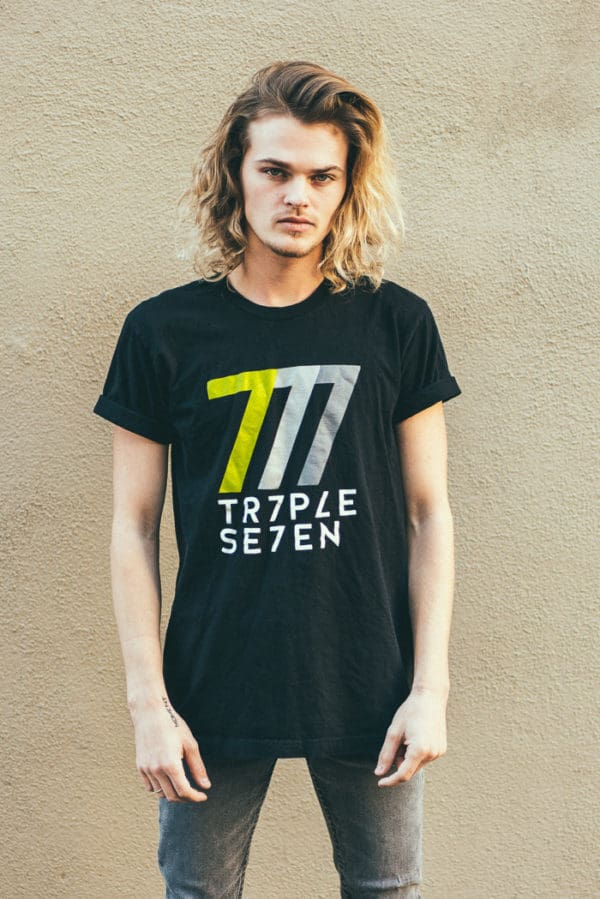 "A man with Yellow hair, showing his front side, looking at front side, wearing a black t-shirt, with ""triple seven"" text on the t-shirt"
