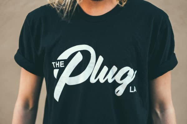 A man with Yellow hair, showing his front side, wearing a black t-shirt, with The Plug LA text on the t-shirt