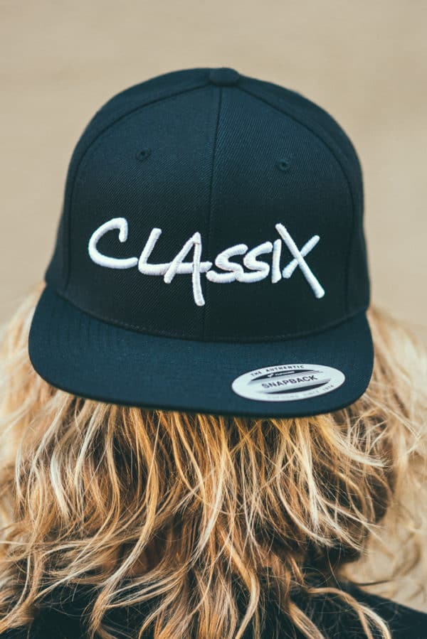 A man with Yellow hair, showing his back, Wearing a flipped Black Cap, with Classix text on it