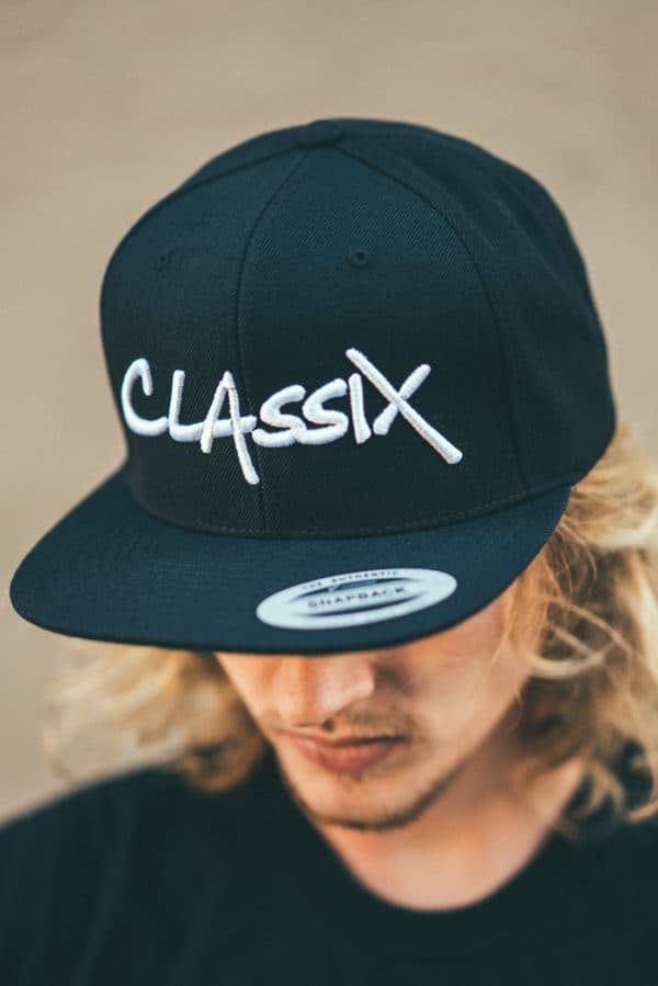A man with Yellow hair, Wearing Black Cap with Classix text on it