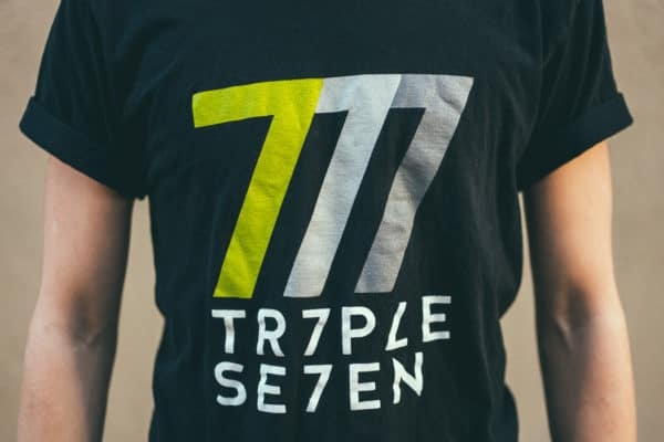 "A man with Yellow hair, showing his front side, wearing a black t-shirt, with ""triple seven"" text on the t-shirt"