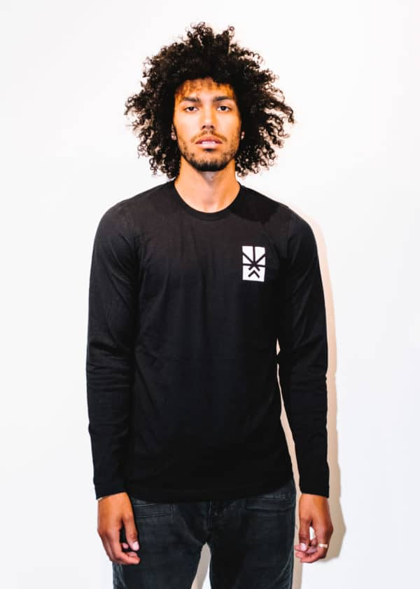 A man with Curly hair, showing his front side, wearing a black t-shirt, with long sleeve, with Project Cannabis logo on the t-shirt