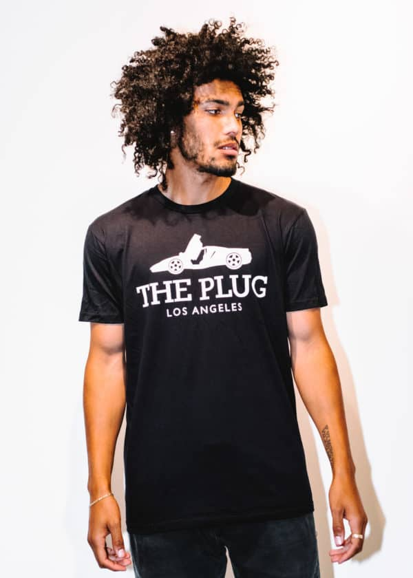 A man with Curly hair, showing his front side, wearing a Black t-shirt, with The Plug LA text on the shirt