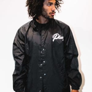 A man with Curly hair, showing his front side, looking to the left side, wearing a Black Jacket, with a long sleeve, with The Plug LA text on the Jacket