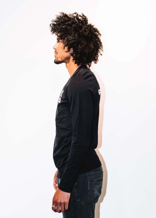 A man with Curly hair, showing his left side, wearing a black t-shirt, with long sleeve