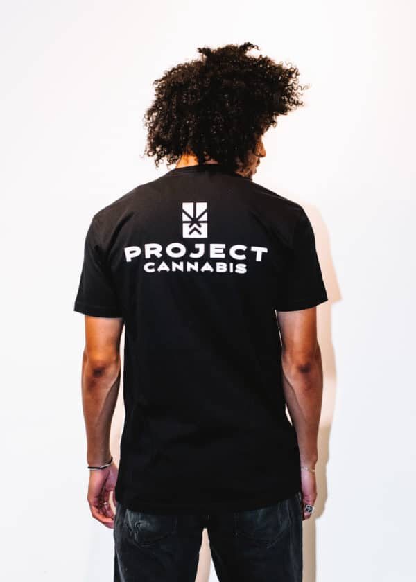 A man with Curly hair, showing his back, wearing a black t-shirt, with Project Cannabis text on the t-shirt