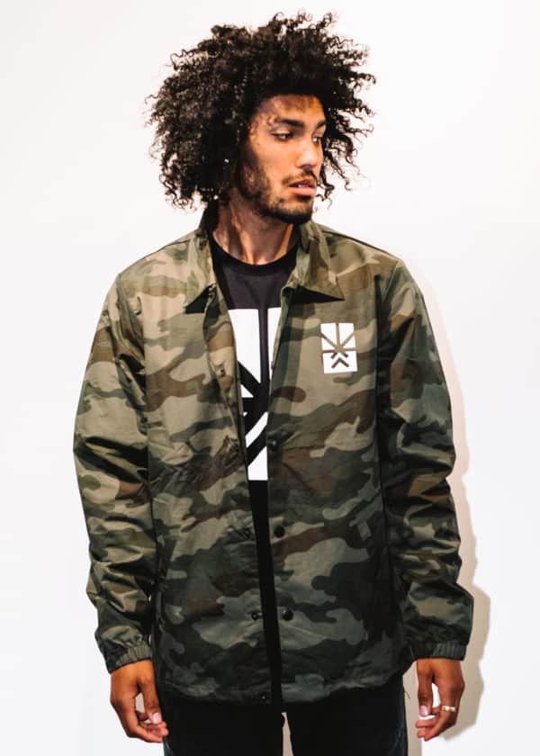 A man with Curly hair, showing his front side, looking to the left side, wearing a Military colors Jacket, with a long sleeve, with Project Cannabis logo on the Jacket