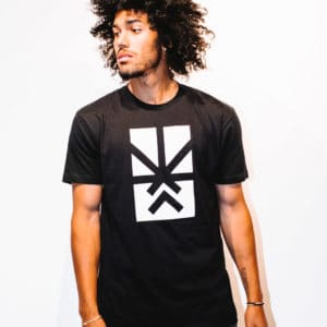 A man with Curly hair, showing his front side, wearing a black t-shirt, with Project Cannabis logo on the t-shirt