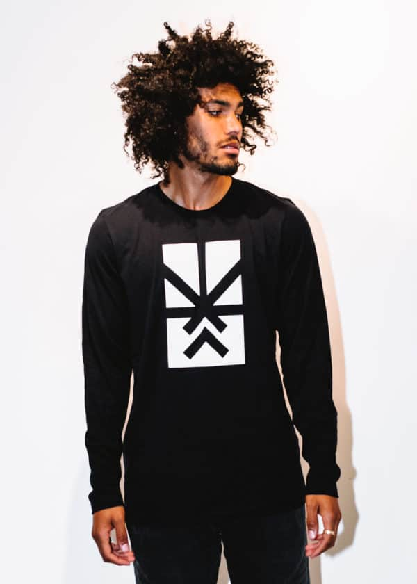 A man with Curly hair, showing his front side, looking to the left side, wearing a Black shirt, with a long sleeve, with Project Cannabis logo on the shirt