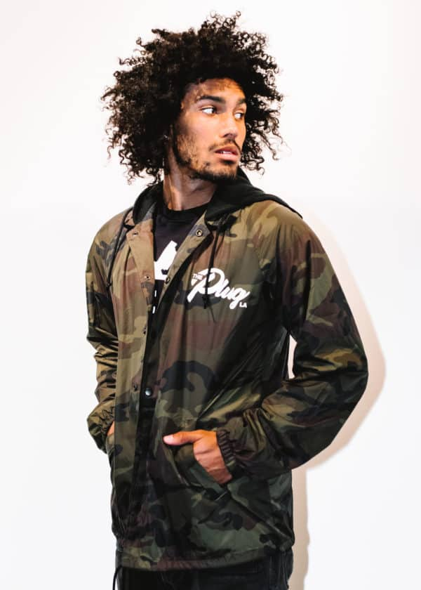 A man with Curly hair, showing his front side, looking to the left side, wearing a Military colors hoodie shirt, with a long sleeve, with The Plug LA text on the shirt
