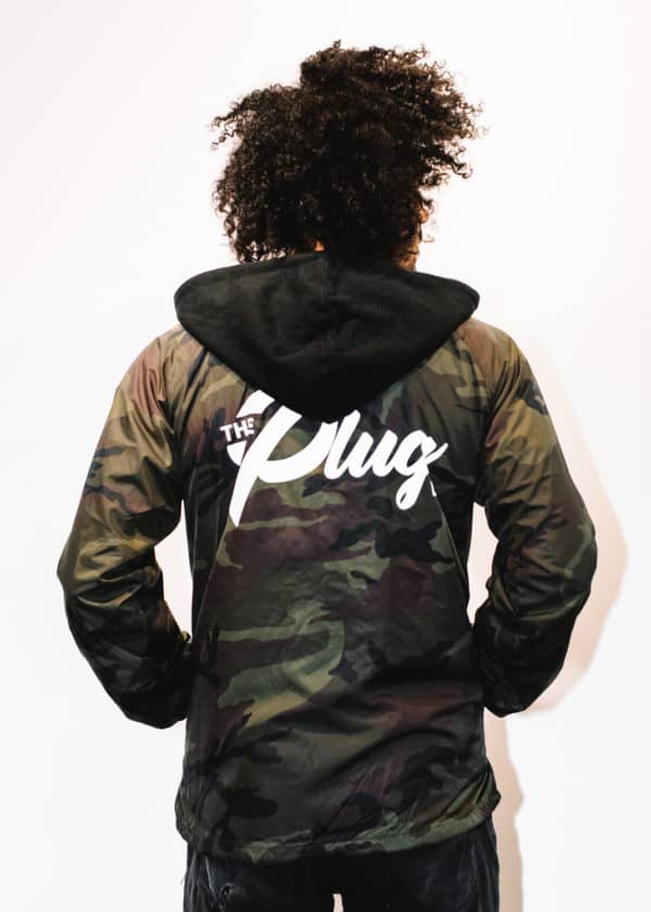 A man with Curly hair, showing his back, wearing a Military colors hoodie shirt, with a long sleeve, with The Plug LA text on the shirt