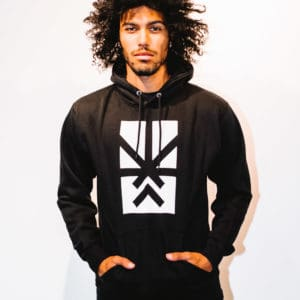 A man with Curly hair, showing his front side, looking to the front side, wearing a black hoodie shirt with a long sleeve, with Project Cannabis logo on the shirt