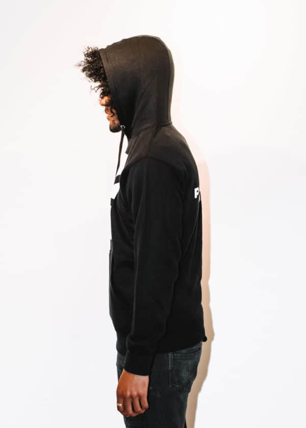 A man with Curly hair, showing his left side, wearing a black hoodie shirt with a long sleeve, with Project Cannabis text on the shirt