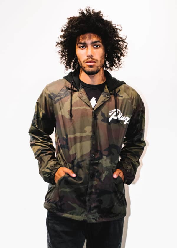 A man with Curly hair, showing his front side, looking to the front, wearing a Military colors hoodie shirt, with a long sleeve, with The Plug LA text on the shirt