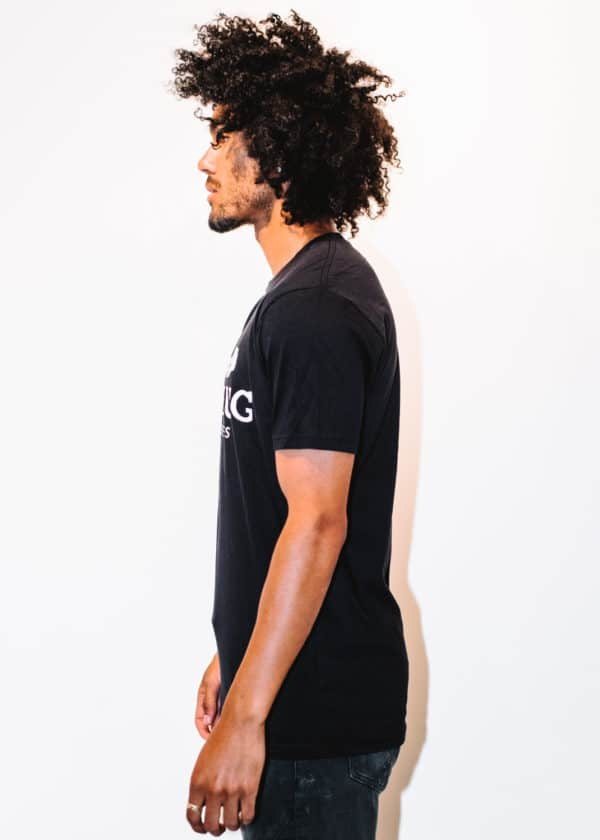 A man with Curly hair, showing his left side, wearing a Black t-shirt, with The Plug LA text on the shirt