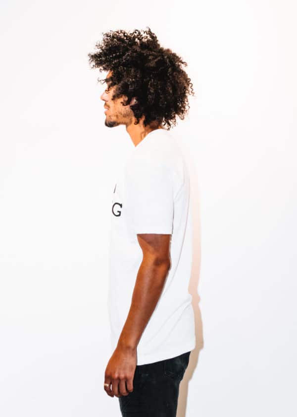 A man with Curly hair, showing his left side, wearing a White t-shirt, with The Plug LA text on the shirt