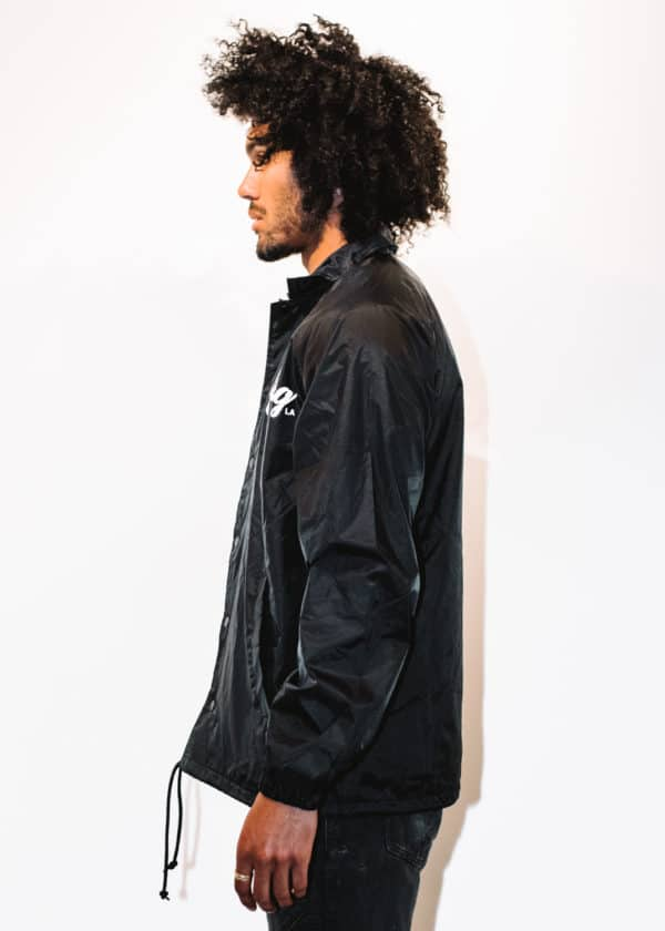 A man with Curly hair, showing his left side, wearing a Black Jacket, with a long sleeve, with The Plug LA text on the Jacket