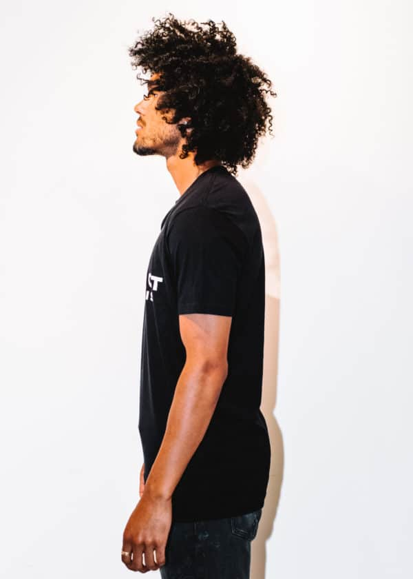 A man with Curly hair, showing his left side, wearing a black t-shirt
