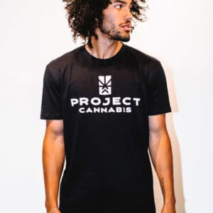 A man with Curly hair, showing his front side, looking to the left side, wearing a black t-shirt, with Project Cannabis text on the t-shirt