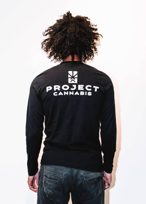A man with Curly hair, showing his back, wearing a black t-shirt, with long sleeve, with Project Cannabis text on the t-shirt