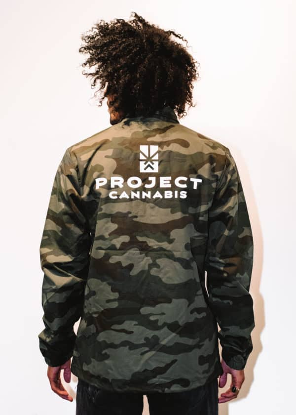 A man with Curly hair, showing his back, wearing a Military colors Jacket, with a long sleeve, with Project Cannabis text on the Jacket