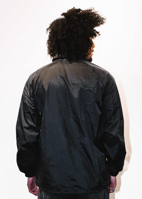 A man with Curly hair, showing his back, wearing a black jacket, with a long sleeve