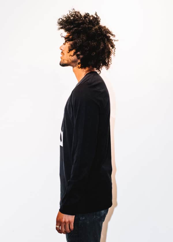 A man with Curly hair, showing left back, wearing a black shirt with a long sleeve, with Project Cannabis logo on the shirt