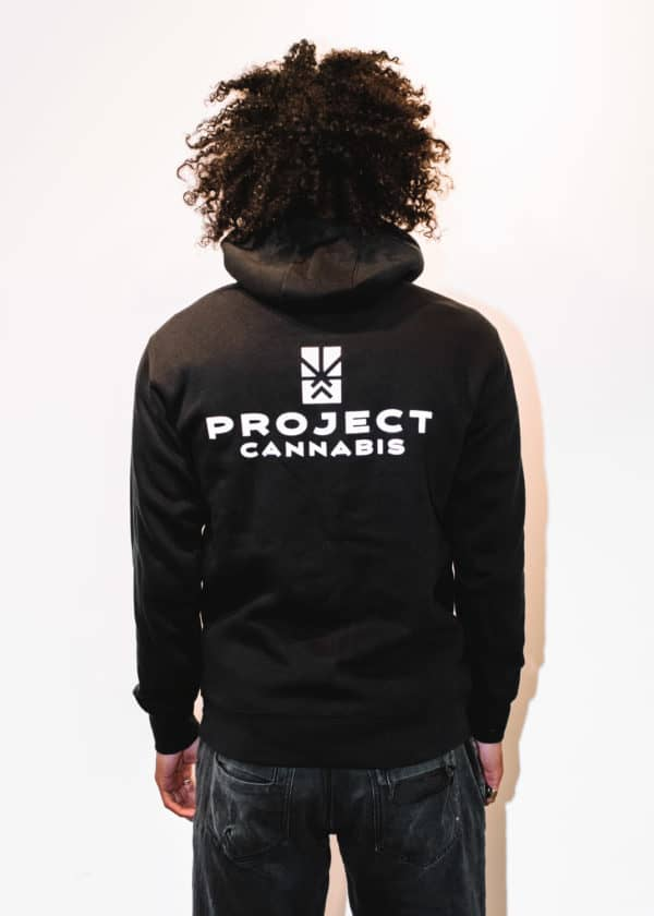 A man with Curly hair, showing his back, wearing a black hoodie shirt with a long sleeve, with Project Cannabis text on the shirt