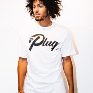 A man with Curly hair, showing his front side, wearing a White t-shirt, with The Plug LA text on the shirt