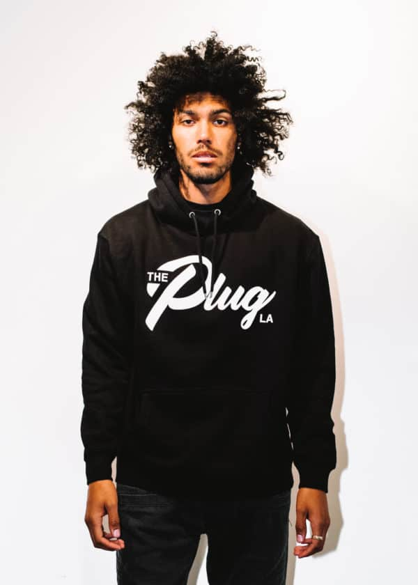 A man with Curly hair, showing his front side, looking to the front, wearing a black hoodie shirt with a long sleeve, with The Plug LA text on the shirt