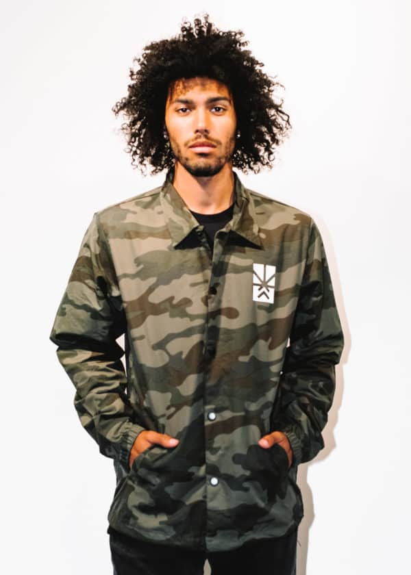 A man with Curly hair, showing his front side, looking to the front side, wearing a Military colors Jacket, with a long sleeve, with Project Cannabis logo on the Jacket
