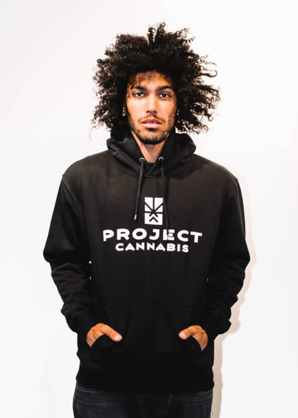 A man with Curly hair, showing his front side, looking to the front, wearing a black hoodie shirt with a long sleeve, with Project Cannabis text on the shirt