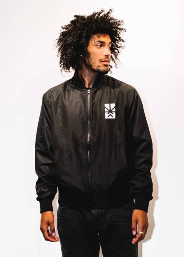 A man with Curly hair, showing his front side, looking to the left side, wearing a Black Jacket, with a long sleeve, with Project Cannabis logo on the Jacket