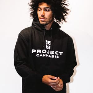 A man with Curly hair, showing his front side, looking to the right, wearing a black hoodie shirt with a long sleeve, with Project Cannabis text on the shirt